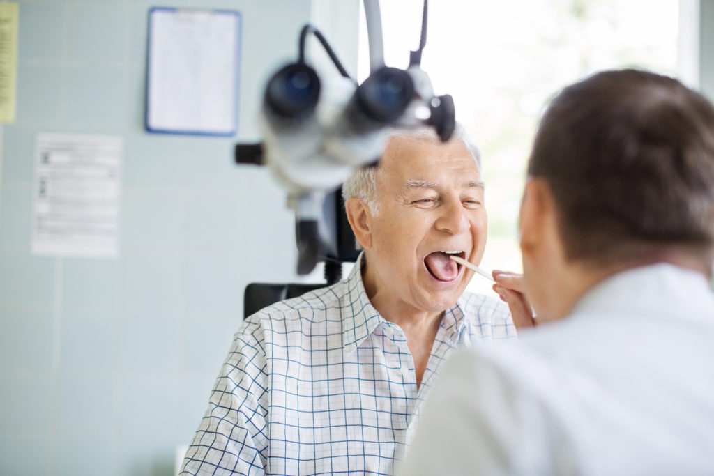 Senior man opening his mouth for the doctor to look in his throat. Male doctor examining sore throat of senior patient in clinic.